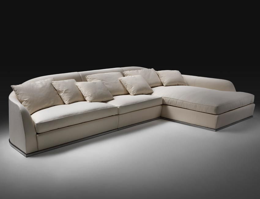 Legless sofa on metal base, for linear or varied configurations. The enveloping back lowers gradually at the sides to become the armrest, gripping the comfortable goosedown seat cushions. A corner element fans out to create a curved composition also suitable for large spaces, perfect for lounge areas and waiting rooms. In the chaise longue version, which can be used to complete the sofa, the armrest is lowered to make room for the large seat cushion. The cushions can be bordered in grosgrain in a range of hues, adding a note of contrasting color that forcefully brings out the lines of the design.