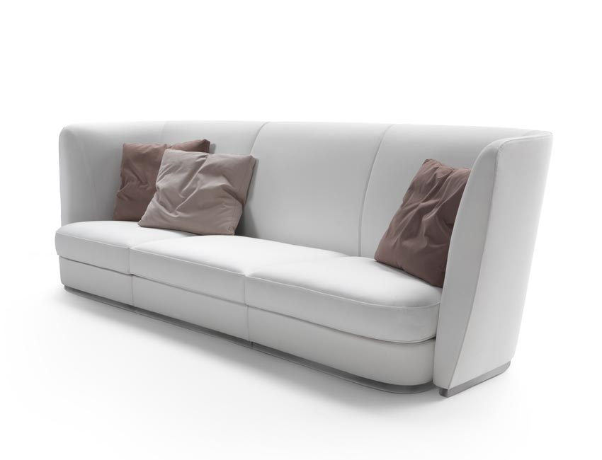 An impressive, oversized sofa that rests on the ground with a slender metal base and features a high upholstered headboard. An almost regal, theatrical presence. The back is abundantly padded, rising well above the head and visually shifting the proportions, putting greater emphasis on height rather than depth. A retro design, but with a streamlined look. Useful to visually fill up large spaces with grace and charm.