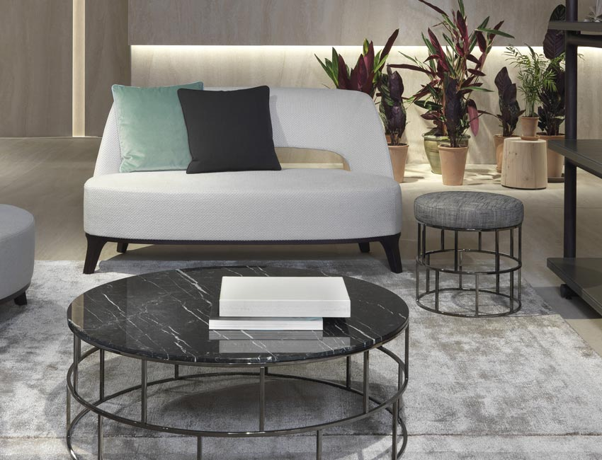 An armchair or a low sofa, it rests on a wooden base raised off the floor by short, slightly splayed legs. The upholstered back is quite compact, leaving a large opening over the seat cushion. Tactful, genteel proportions. A solid image, but light.