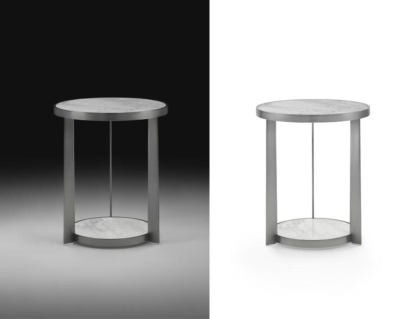 A refined table with an oval shape. The metal structure supports two marble tops, one at the floor and one raised, set into the double metal frame. Of ample size, attenuated by the rounded edges, the double surface offers real functional advantages. The range of finishes for the metal and the variety of the types of marble in the catalogue make it a truly versatile creation.