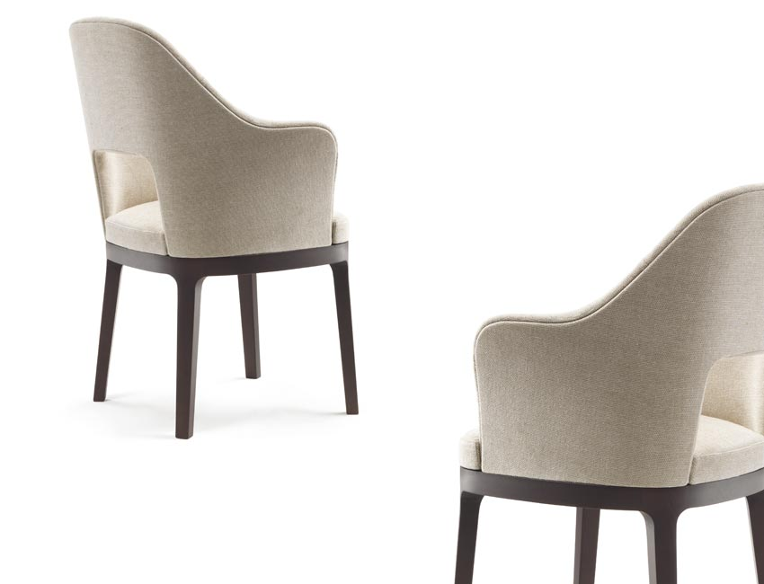 A simple chair, or a dining chair with armrests. With its base in solid wood on square legs, firm upholstery and back with a lower opening, Judit conveys a sense of great composure and harmony. The padded seat goes well with large, impressive dining tables. The two versions can be mixed, perhaps by opting to use the armchairs only at the heads of the table.